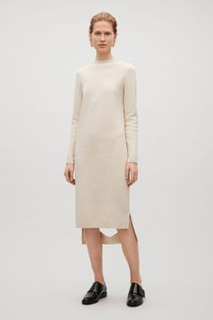 Designed with a cut-out detail at the bottom of the back hem, this dress is made from milano knitted cotton with a dense, tactile quality. A straight fit, it has extra-long sleeves, clean finished edges and a tightly ribbed neckline.