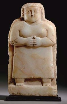 A SOUTH ARABIAN ALABASTER RELIEF  CIRCA 3RD-1ST CENTURY B.C.  Carved with a woman standing on a rectangular plinth, her hands held together below her breasts, wearing a long tunic, her face with large almond-shaped eyes, the pupils articulated, the eyebrows grooved, with a long straight nose and a small mouth; 11 in. (27.9 cm.) high