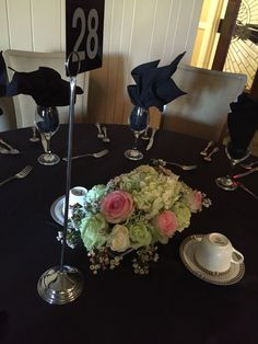 Centerpieces with roses, hydrangea and wax flower.