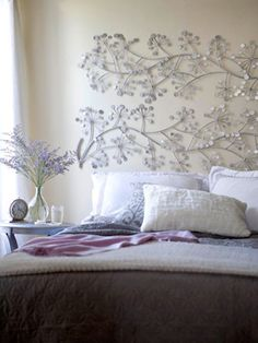 DIY Headboard. Two metal decorative wall panels spray painted silver and hung together length-wise to create a chic and cheap headboard.