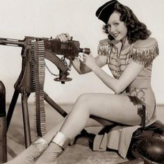 Ann Miller with an Browning caliber machine gun in a colorized wartime pin-up