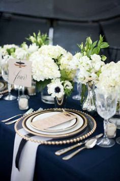Gold and white table decor with hydrangeas and blue table cloth for a romantic garden wedding.
