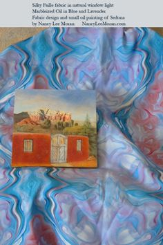 """This marbleized fabric flows quietly, blue into lavender, with some hints of warm earth colors. In the yard version, it appears like a row of blue-rimmed jewels. Silky Faille fabric in natural window light shows """"Marbleized Oil in Blue and Lavender"""" fabric and a small oil painting of Sedona, both by Nancy Lee Moran.  Click the photo to buy the design as fabric, wallpaper, and gift wrap on Spoonflower."""