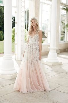 Six alternative wedding dresses for unconventional brides | This romantic Needle & Thread dress features a soft pink and ivory ombre effect and a voluminous skirt that is sure to turn heads. Constructed from 100% nylon tulle, the skirt has been cut in a way that increases the fullness towards the hem to create dramatic movement, and 3D floral embroidery delicately trails down the gown. Unique and colourful, this garment has an elegant boho vibe that would perfectly suit a rustic summer…