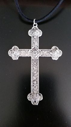 This necklace is 18 1/ inches long. It has a silver metal cross pendent on an 18 1/2 inch long black cord.  https://www.etsy.com/listing/222625474/silver-metal-cross-necklace-cross