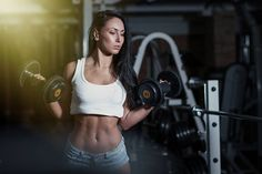 A woman is lifting dumbbells.