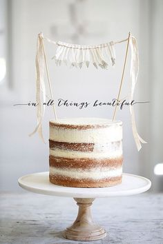 Glitter-dipped feather cake bunting on naked cake.