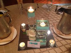 Wedding table decor. Glass vase centerpieces with water, white roses, tea light, floating candles, on a square mirror with rhinestone ribbon embellishment. Crafted by me. #craftsByMel Tiffany blue wedding theme.