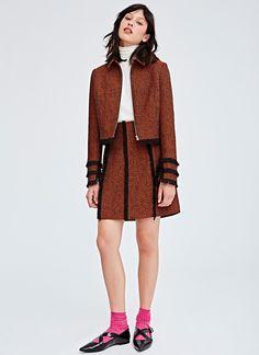 Chaqueta corta entallada en un exquisito tejido tweed con textura jaspeada. Cuello camisero, manga larga y cierre central de cremallera metálica. Remate de fleco corto en contraste, que confiere un aire artesanal a la silueta.