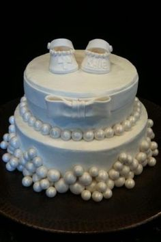 Baby Bootie cake covered in buttercream frosting with fondant baby booties, pearls and bow.