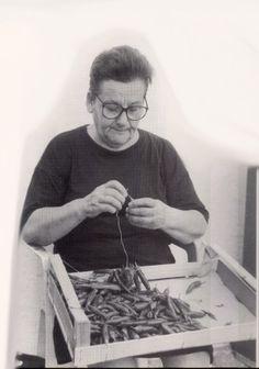 Donne a lavoro: Una signora al lavoro con una collana di peperoncini