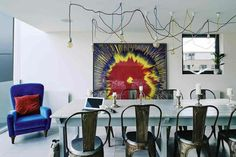 mesas de comedor moderno, comedor extravagante con detalles en azul intenso, lámparas vintage muy originales, decoración atractiva en la pared
