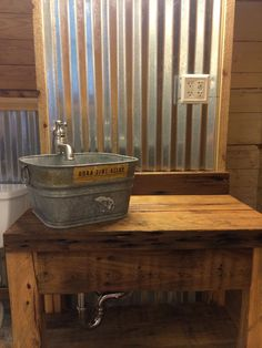 Corrugated tin walls with cypress vanity and galvanized bucket.