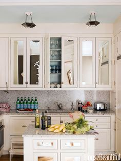 Antiqued mirrored glass on cabinet doors enlarges the small kitchen in a Brooklyn townhouse decorated by Jonathan Berger. The granite countertops and backsplash in Imperial White are from E. Stone.   - HouseBeautiful.com
