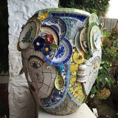 I made this mosaic urn with three faces for Rosemary.The three faces represent three generations (daughter, mother, grandmother) and are made from pieces of china collected from Rosemary's family. I have added my own ceramic flowers and leaves as well as beads, and glass tiles to assemble the collection of china into a harmonious whole.
