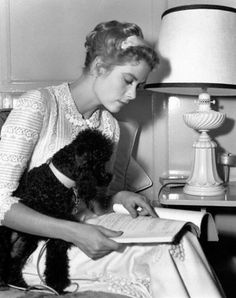 Grace Kelly reading with a friend.