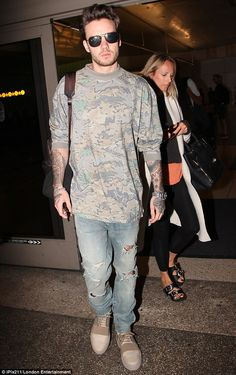 Stony faced: Liam Payne, 23, looked weary as he arrived at LAX Airport on Tuesday as it em...