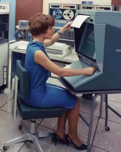 woman working with an old mainframe computer in the 1960s.