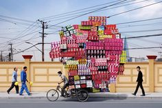"Apparently, some people in China have never heard of U-Haul. They are, however, amazingly efficient in the way they pack and move all their inventory on a tiny little bike. 'Manufactured Totems' is a series by Alain Delorme which brilliantly portrays the pressure Shanghainese migrant workers face. Piles of products labeled ""Made in China"" are stacked up to produce gargantuan sculptures, symbolizing their ever-increasing fetish with objects. The vertical nature of these items echoes the…"