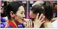 101c: This is a picture of a coach consoling American gymnast Jordyn Wieber. Both the coach and the gymnast are equally featured in the photo. It captures an instant of raw emotion and has a shallow depth of field to draw more attention to the two women. No national identity is clearly depicted in the photo.