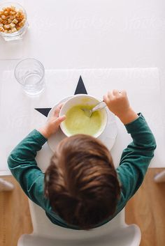 Overhead of a young boy eating a vegetable puree soup for lunch at home. by BONNINSTUDIO