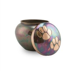 - Raku styled metal pet urn with 2 bronze paw prints accents on the lid. Raku coloring design is created when metal is fired in a kiln, then left out to oxidize into a unique, iridescent array of colo