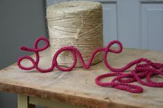 What a great idea! twist wire into a word, then wrap in yarn for a cute decoration.