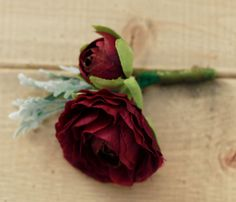 Perfect Romantic touch to your wedding or special event. Can be used as a boutonniere or very small chest corsage. This boutonniere includes: - Plum Burgundy Ranunculus - Plum Burgundy accent Blossom