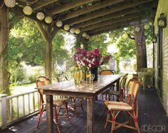 Keith McNally house on Martha's Vineyard Bistro chairs surround a reclaimed-wood table on the front porch; the lanterns are from Pearl River.    - ELLEDecor.com