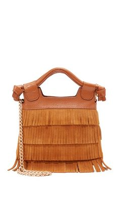 Tiered fringe adds bohemian flair to this suede Foley + Corinna cross-body bag. Magnetic top line and logo-lined interior. Rolled leather handles and hideaway chain cross-body strap.