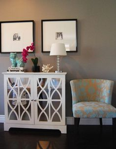 Lovely foyer design with gray walls paint color, white mirrored cabinet, black  white photos in black gallery frames, turquoise blue foo dog, turquoise blue damask chair and orchid.