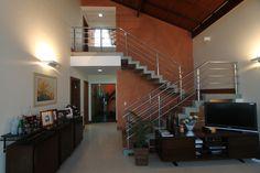 Projetamos esta sala com teto inclinado, emoldurada pela escada em concreto recortada.