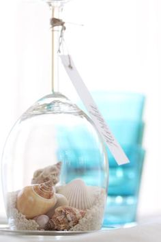 Join our Facebook!  https://www.facebook.com/AAHsf    Love this idea..wine glass with seashells, sand, place card / Table Decor
