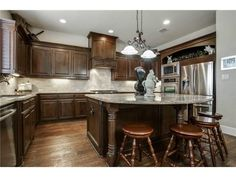 Stunning brown kitchen with light granite countertops // tons of prep space, large island with seating, stainless appliances