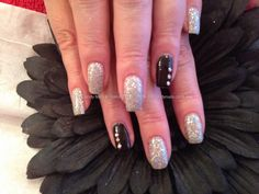 Acrylic nails with silver glitter gel polish and ring fingers in black gel polish with crystals