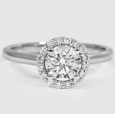 An intricate halo of pavé-set diamonds embraces and accentuates the center diamond of this brilliant antique-style ring. #BrilliantEarth