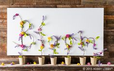 Bring beautiful spring flowers into your living room! First, spray paint the edges of a white canvas gold. Next, cut wisteria garland and form into letters using floral wire. Hot glue the letters onto the canvas.  Finally, pick colorful flowers from floral garland and hot glue onto letters.