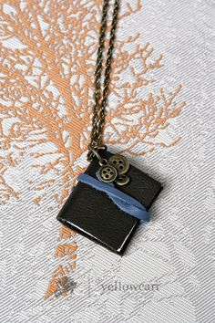 I might have to make my own.  These mini-book-necklaces are either a)$$ or b)leather.  But here's another cute one.