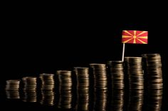 macedonian flag with lot of coins isolated on black background