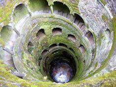 POÇO INICIÁTICO( SINTRA)  Uma galeria subterrânea com uma escadaria em espiral, sustentada por colunas esculpidas, por onde se desce até ao fundo do poço. A escadaria é constituída por nove patamares separados por lances de 15 degraus cada um, invocando referências à Divina Comédia de Dante e que podem representar os 9 círculos do inferno, do paraíso, ou do purgatório.