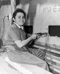 1943: Portrait of American factory worker Winifred Thompson, who is a Navajo, using a riveter to assemble an airplane at the Consolidated Aircraft Corporation during World War II, San Diego, California. She wears a hairnet and a canvas uniform. (Photo by R. Gates/Hulton Archive/Getty Images)