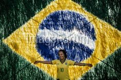 BRAZIL, Salvador : A woman poses in front a Brazilian flag in a street in Salvador on June 17, 2014, prior the match opposing Brazil to Mexico during the 2014 FIFA World Cup. AFP PHOTO / DIMITAR DILKOFF