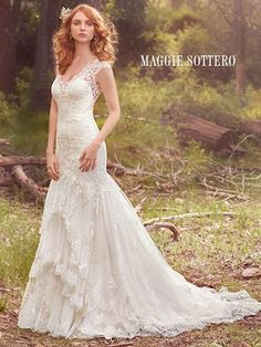 Maggie Sottero Zalia. A three-tiered skirt hemmed in scalloped lace appliqu�s adds romance and whimsy to this classic fit-and-flare. Lace motifs adorn the bodice, illusion V-neckline, illusion straps, and illusion open-back. Finished with covered buttons over zipper closure.