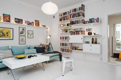 white-swedish-apartment-interior-with-blue-pastel-sofa-and-white-table-also-beautiful-rounded-pendant-lamsp-and-large-bokshelf-on-the-wall-with-white-floor-and-lamps-decoration-on-the-shelf-above-the-sofa-918x613.jpg (918×613)