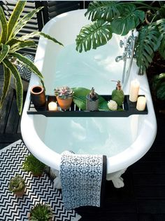 take a bath with some relaxing candles and adorable plants. a chic tub doesn't hurt!