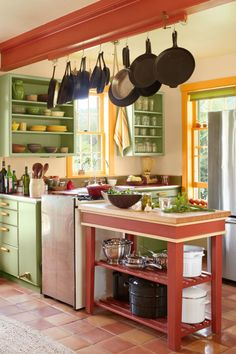 Colorful Accents:  Bright pops of color can easily transform your kitchen. For instance, this New Hampshire farm home's vibrant green cabinets work well beside the brick-red trim and island.