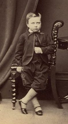 Boy July 1864 This young boy wears a suit with a Zouave-style jacket (fastened only at the top and with a curved front exposing the waistcoat below). Small collars were common at mid-century. He has a small turn-over collar and a narrow bow tie.