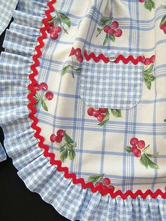 Ruffles and rick rack~ a fun and cheerful little apron with vintage flair. Done in cute plaid, gingham and cherry prints and embellished with a pocket and a ruffled hem.
