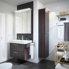 A white bathroom with GODMORGON sink cabinet in black brown and MOLGER trolley in birch.