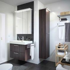 Ein weißes Badezimmer mit GODMORGON Waschbeckenschrank mit 2 Schubladen in Schwarzbraun, GODMORGON Hochschrank in Schwarzbraun und MOLGER Rollwagen in Birke